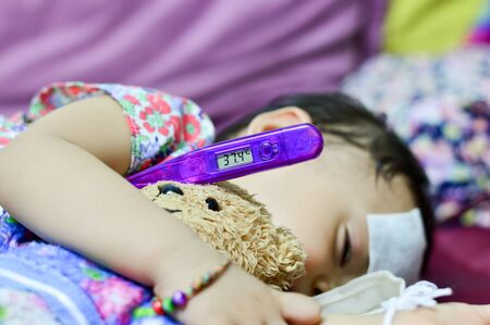 Sick baby lying measuring electric thermometer 스톡 콘텐츠