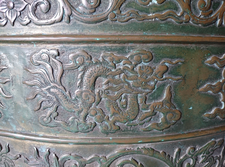 Old metal relief - probably bronze - in buddhist temple of Ninh Binh, Vietnam, South-East Asia. Highly decorative surface covered with dragons and floral ornament pattern. Green and red metallic texture is antique, even ancient.