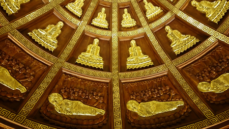Shiny metal relief silhouettes of Buddha- probably gold - in buddhist temple of Ninh Binh, Vietnam, South-East Asia. Highly decorative ceiling covered with sitting and laying figures radial pattern. Yellow metallic texture is shiny, yet traditional.
