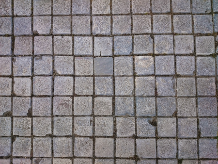 Square grey tiles on the floor or wall. Rusty gray background with irregular bricks. Concrete pavement urban pattern. Cement tiled sidewalk outdoors.