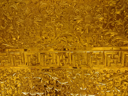 Shiny metal relief - probably gold - in buddhist temple of Ninh Binh, Vietnam, South-East Asia. Highly decorative surface covered with floral ornament pattern. Yellow metallic texture is shiny, yet traditional with line of swastika. Foto de archivo