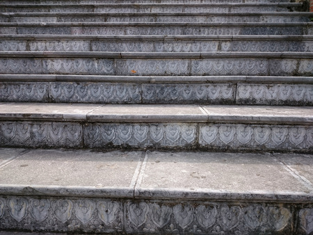 Stone stair with carved grey steps. Ascending steps outdoors in the vietnamese style pattern. Brown staircase rising up to the temple with floral pattern low relief. Foto de archivo