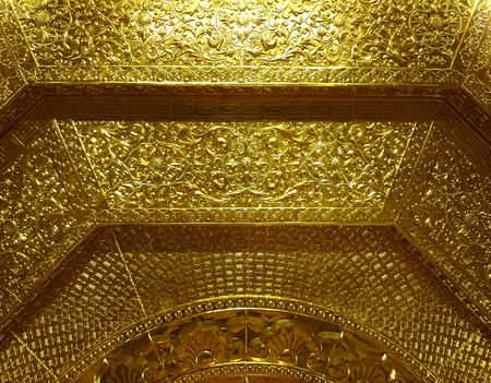 Shiny metal relief - probably gold - in buddhist temple of Ninh Binh, Vietnam, South-East Asia. Highly decorative surface covered with floral ornament pattern. Yellow metallic texture is shiny, yet traditional. Foto de archivo
