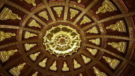 Shiny metal relief silhouettes of Buddha- probably gold - in buddhist temple of Ninh Binh, Vietnam, South-East Asia. Highly decorative ceiling covered with sitting figures radial pattern. Yellow metallic texture is shiny, yet traditional.