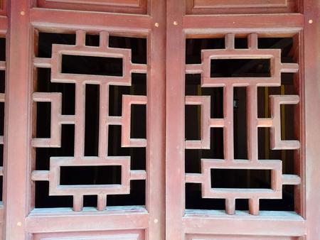 Window or door lattices, slightly open, wooden and red colored. Black doorway of ancient Vietnamese temple.