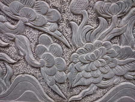 Old stone relief in buddhist temple in Vietnam, South-East Asia. Decorative grey surface covered with flowers and trees, floral ornament pattern.