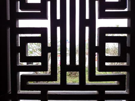 Window lattice, wooden or metal, black colored. Sunlit view out of ancient Vietnamese temple. Foto de archivo