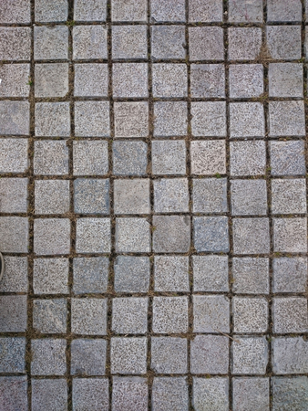 Square grey tiles on the floor or wall. Rusty gray background with irregular bricks. Cement tiled sidewalk outdoors. Concrete pavement urban pattern.