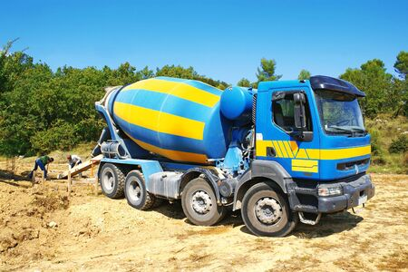 Concrete truck delivering concrete used for the foundations of a house.