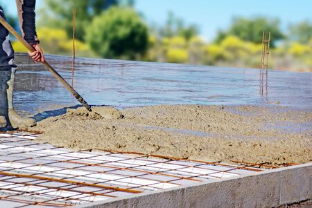 Manual distribution of concrete on the floor of a house under construction.