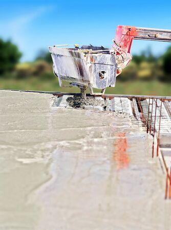 Concrete mixer on telescopic arm for the construction of a concrete floor.