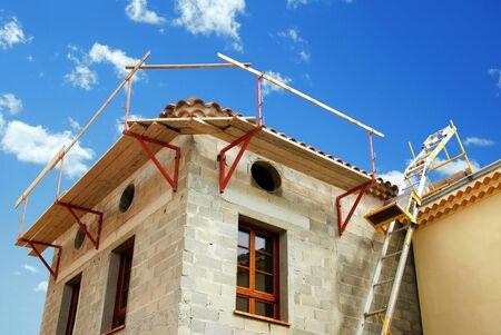 Scaffolding and mason ladder on a house under construction. Zdjęcie Seryjne