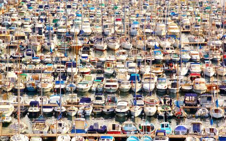 Numerous boats moored in pontoon of a marina.