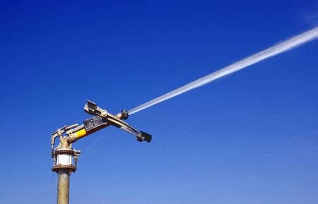 Irrigation water jet on blue sky background.
