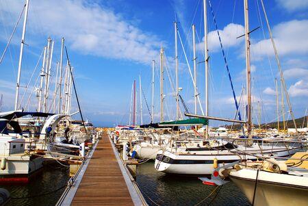 Pleasure boats moored at the harbor along a pontoon.