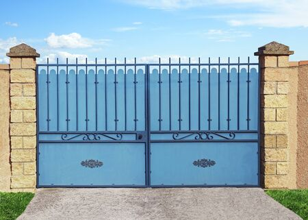 Blue metal gate attached to stone pillars. Stock Photo