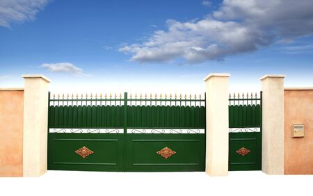 Green metal gate and wicket on an unhappy blue sky background. Archivio Fotografico