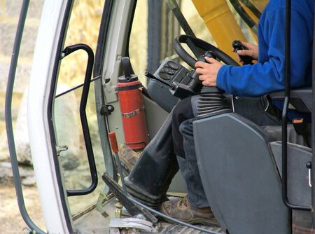 Driving position of a backhoe in action. Archivio Fotografico - 150293578