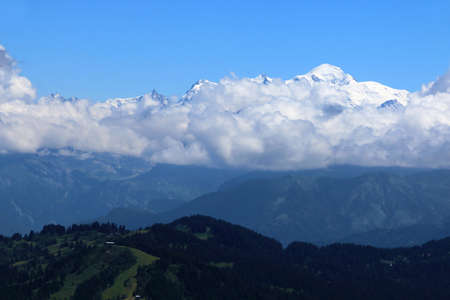 The snow-capped Mont Blanc above the clouds, against a blue sky. Archivio Fotografico