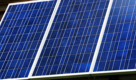 Panel of blue photovoltaic cells receiving sunlight.