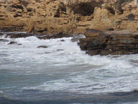Sea waves rolling against a rocky shore, water shining in the sun, splashing. Spain, Mediterranean coast Stock fotó - 135501474