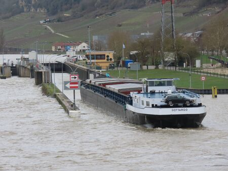 Grevenmacher, Luxembourg March 16, 2019. River cargo boat entering lock on Moselle river on a spring day with high water