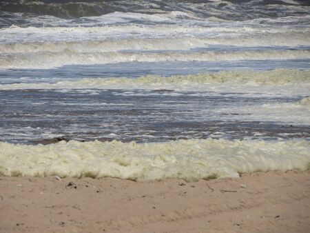 Stormy North sea waves creating striped pattern, sea foam, sand on beach Stockfoto