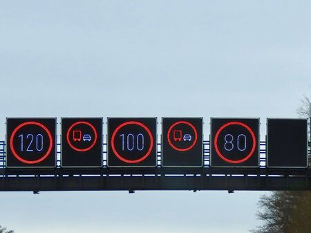Speed limit signs on German no limit autobahn 80, 100, 120 km per hour according to lines, overtaking prohibited for trucks. White and red LED lamps on a black board against misty sky 免版税图像