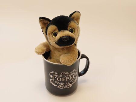 Plush toy German shepherd puppy sitting in a black vintage coffee mug, off white background