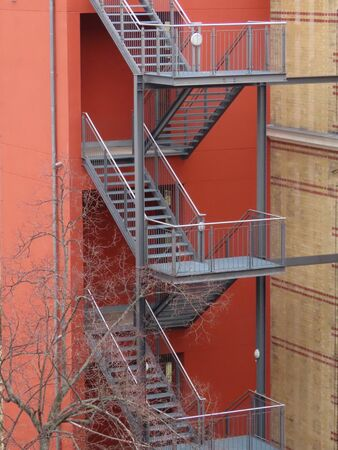 Three stories high grey metal fire escape steps by red wall, can see them through leafless tree in early spring