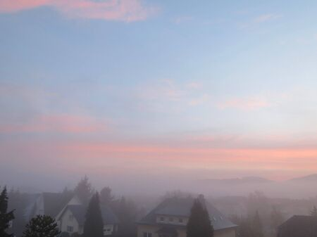 Soft colors of dawn sky - blue with pink and white clouds, come buildings and trees in shade at the bottom of photo