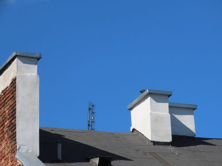 White chimneys on a black roof, one of them has red brick side, a radio or tv antenna on the roof. Blue sky background as copy space