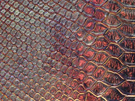 Background texture: light from various angles on a crocodile pattern embossed holographic surface creates different colors, selective focus area changed for each photo. Dark red. Stock Photo