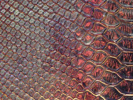 Hintergrundtextur: Licht aus verschiedenen Winkeln auf einer holografischen Oberfläche mit Krokodilprägung erzeugt verschiedene Farben, der selektive Fokusbereich ändert sich für jedes Foto. Dunkelrot. Standard-Bild