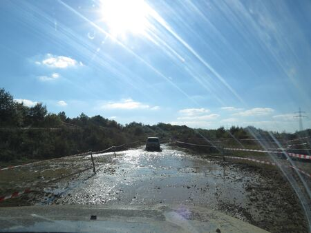 All terrain training event. Passenger view to mud water covered trail, preceding car, sun shining on dirt covered windscreen