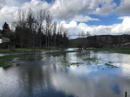 High water of spring floods covering meadow, blue sky with white clouds reflecting