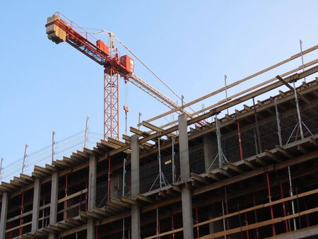 Construction site of a new apartment building, facade with scaffolding structures, red tower crane