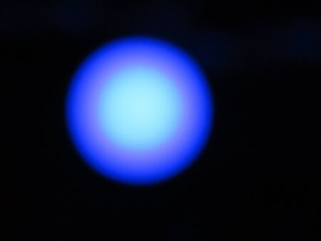 Defocussed photo of blue light bulb on a dark background that gives a slight pulsating optical illusion