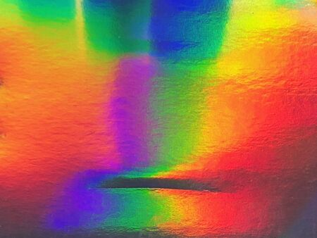 Background texture: light reflecting on a flat holographic surface, random spots of different colors make bright psychedelic effect