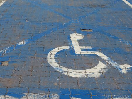 Disabled parking place at some shop: white wheelchair user icon on a blue background repeatedly painted on cobble tiles