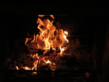 Fire burning in fireplace, close up of orange flames eating firewood Stock fotó