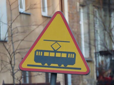Faded road caution sign Warning tramway tracks ahead: yellow triangle with red border and black electric vehicle silhouette. Old brick building in blurred background, bright spring day