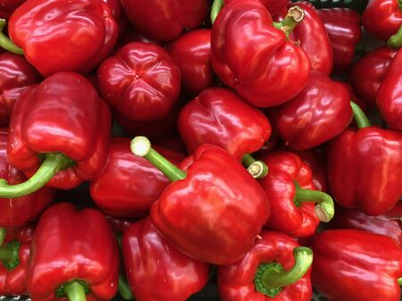 Red bell peppers, also sweet peppers, paprika, on market: close up filling the whole photo