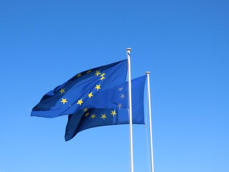 Two European Union EU flags bold and proud floating in the wind, against sunny blue sky Banco de Imagens