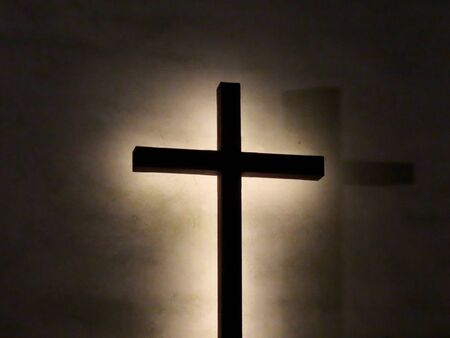 Dark Christian cross with light behind it against light colored wall at night