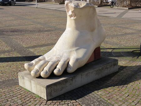 Foot from statue of Roman Emperor Constantin the Great, who was born in Trier, copy from antique roman art in Konz market square, Germany, sunny spring day