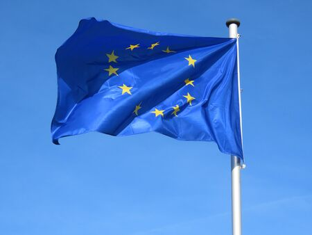European Union EU flag bold and proud floating in the wind, against sunny blue sky Banco de Imagens