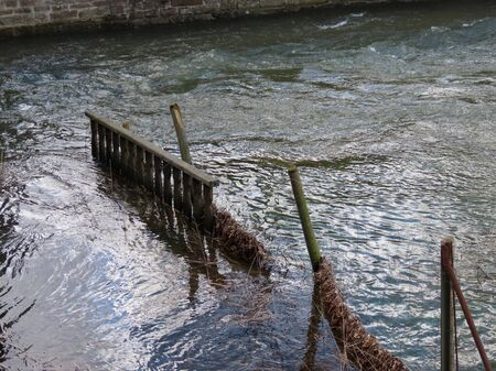 High water of spring floods rushing through an old broken fence