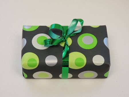 Package gift wrapped in grey paper with green circles, tied with green shiny ribbon