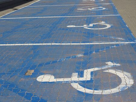 Several disabled parking places at some shop: white wheelchair user icon on a blue background repeatedly painted on cobble tiles Stock Photo
